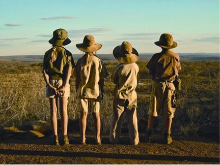 Kids on safari looking out over African savannah