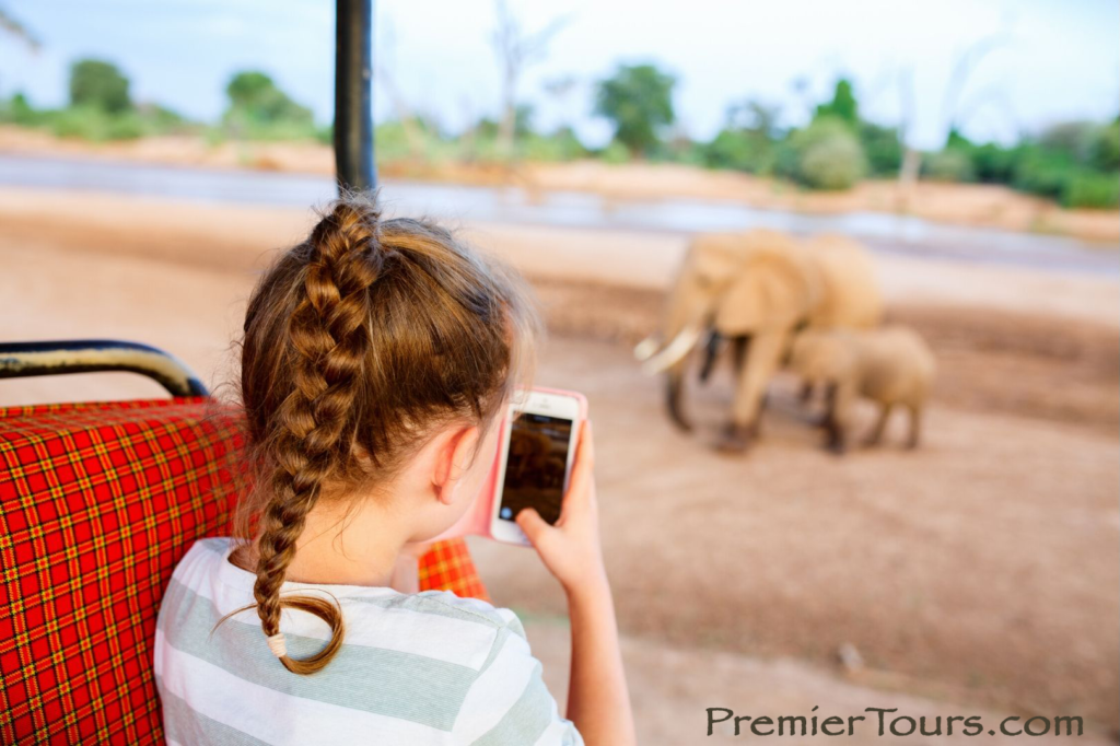 Will I Be Able to Use My Smartphone on Safari? Child on phone on game drive.